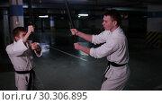Купить «Two men in kimono training their kendo skills on a parking lot. Sword fight», видеоролик № 30306895, снято 8 июля 2020 г. (c) Константин Шишкин / Фотобанк Лори