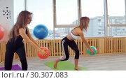 Купить «Young women doing fitness in the studio holding a ball», видеоролик № 30307083, снято 25 марта 2019 г. (c) Константин Шишкин / Фотобанк Лори
