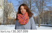 Amazing young woman in coat and colorful knitted scarf posing looking at the camera during sunny day on blue sky background. Стоковое видео, видеограф Ольга Балынская / Фотобанк Лори
