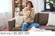 Купить «unhappy sick woman in scarf coughing at home», видеоролик № 30307191, снято 10 марта 2019 г. (c) Syda Productions / Фотобанк Лори