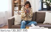 Купить «sick young woman in scarf drinking hot tea at home», видеоролик № 30307195, снято 10 марта 2019 г. (c) Syda Productions / Фотобанк Лори