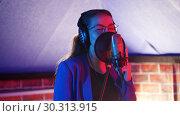 Купить «A young woman in glasses and headphones singing in the studio», видеоролик № 30313915, снято 23 марта 2019 г. (c) Константин Шишкин / Фотобанк Лори