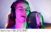 Купить «A young woman in headphones singing in the studio. Neon lighting», видеоролик № 30313947, снято 23 марта 2019 г. (c) Константин Шишкин / Фотобанк Лори