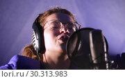 Купить «A young emotional woman in headphones singing song in the studio looking in the camera», видеоролик № 30313983, снято 23 марта 2019 г. (c) Константин Шишкин / Фотобанк Лори