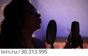Купить «A young woman in glasses and headphones standing by the mic and singing a song», видеоролик № 30313995, снято 23 марта 2019 г. (c) Константин Шишкин / Фотобанк Лори