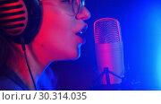 Купить «A young emotional woman in headphones singing in the studio. Neon lighting», видеоролик № 30314035, снято 4 июля 2020 г. (c) Константин Шишкин / Фотобанк Лори