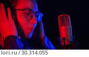 Купить «A young woman in glasses and headphones comes to the mic stand and starts singing», видеоролик № 30314055, снято 23 марта 2019 г. (c) Константин Шишкин / Фотобанк Лори