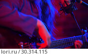 Купить «A young woman goes through the strings of guitar and singing a song in neon lighting», видеоролик № 30314115, снято 23 марта 2019 г. (c) Константин Шишкин / Фотобанк Лори
