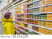 Купить «Russia Samara March 2019: A beautiful mature woman thought about buying tea supermarket. Text in Russian: tea, black, may, discount», фото № 30314235, снято 1 марта 2019 г. (c) Акиньшин Владимир / Фотобанк Лори