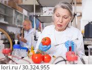 Купить «Woman biochemist checking fruits and vegetables», фото № 30324955, снято 24 января 2019 г. (c) Яков Филимонов / Фотобанк Лори