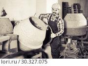 Купить «working man practicing his skills with mixing unit at workshop», фото № 30327075, снято 17 января 2017 г. (c) Яков Филимонов / Фотобанк Лори