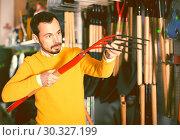 Купить «cheerful guy deciding on best hayfork in garden equipment shop», фото № 30327199, снято 2 марта 2017 г. (c) Яков Филимонов / Фотобанк Лори