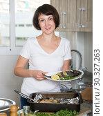 Купить «Woman with dorado fish in baking tray», фото № 30327263, снято 22 ноября 2018 г. (c) Яков Филимонов / Фотобанк Лори
