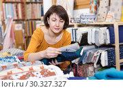 Купить «Woman looking for cloth in shop», фото № 30327327, снято 7 февраля 2019 г. (c) Яков Филимонов / Фотобанк Лори