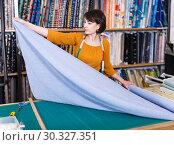 Купить «Saleswoman measuring and cutting off piece of cloth», фото № 30327351, снято 7 февраля 2019 г. (c) Яков Филимонов / Фотобанк Лори