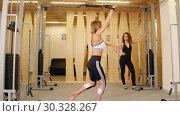 Купить «Young women doing fitness in the gym. A woman doing strength exercises on her hands. Another woman watching her», видеоролик № 30328267, снято 25 марта 2019 г. (c) Константин Шишкин / Фотобанк Лори