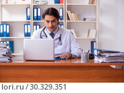 Young handsome doctor working in the clinic. Стоковое фото, фотограф Elnur / Фотобанк Лори