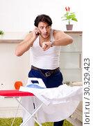 Купить «Young man ironing in the bedroom», фото № 30329423, снято 29 ноября 2018 г. (c) Elnur / Фотобанк Лори