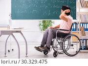 Купить «Young handsome man in wheelchair in front of chalkboard», фото № 30329475, снято 23 ноября 2018 г. (c) Elnur / Фотобанк Лори