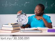 Купить «Black female student in front of chalkboard», фото № 30330091, снято 26 октября 2018 г. (c) Elnur / Фотобанк Лори