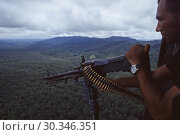 Купить «PANAMA Darien Gap -- 10 Jul 1997 -- A Panamanian frontier policeman mans an M-60 light machine gun about a helicopter over the jungles of the Darien Gap...», фото № 30346351, снято 22 августа 2019 г. (c) age Fotostock / Фотобанк Лори