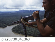Купить «PANAMA Darien Gap -- 10 Jul 1997 -- A Panamanian frontier policeman mans an M-60 light machine gun about a helicopter over the jungles of the Darien Gap...», фото № 30346363, снято 22 августа 2019 г. (c) age Fotostock / Фотобанк Лори