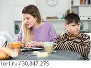 Купить «Young mother working at laptop and unhappy preteen son», фото № 30347275, снято 9 февраля 2019 г. (c) Яков Филимонов / Фотобанк Лори