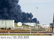 Deer Park, Texas / United States - March 19, 2019: Multiple tanks burn at Deer Park chemical facility. A massive plume of black smoke hangs over Houston. Редакционное фото, фотограф Ирина Кожемякина / Фотобанк Лори