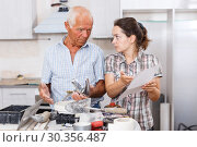 Купить «Perplexed woman and senior man with mixer tap and paper», фото № 30356487, снято 19 июня 2018 г. (c) Яков Филимонов / Фотобанк Лори