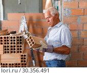 Купить «Man checking brick for masonry», фото № 30356491, снято 19 июня 2018 г. (c) Яков Филимонов / Фотобанк Лори