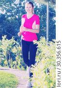 Купить «Athletic female in pink T-shirt is jogging», фото № 30356615, снято 10 июня 2017 г. (c) Яков Филимонов / Фотобанк Лори