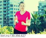Купить «Woman in pink T-shirt is jogging», фото № 30356627, снято 10 июня 2017 г. (c) Яков Филимонов / Фотобанк Лори