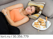 Young woman is having a stomach ache after overeating. Стоковое фото, фотограф Яков Филимонов / Фотобанк Лори