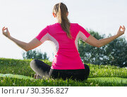 Купить «Adult female in pink T-shirt is sitting her back and practicing meditation», фото № 30356827, снято 10 июня 2017 г. (c) Яков Филимонов / Фотобанк Лори