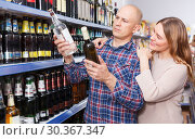 Family couple choosing alcohol products in hypermarket. Стоковое фото, фотограф Яков Филимонов / Фотобанк Лори