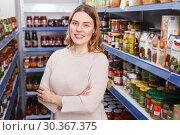 Купить «Portrait of positive female customer near shelves with pickle goods», фото № 30367375, снято 11 апреля 2018 г. (c) Яков Филимонов / Фотобанк Лори