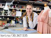 Купить «Portrait of woman designer who is standing on her workplace in time designing new collection», фото № 30367535, снято 5 мая 2018 г. (c) Яков Филимонов / Фотобанк Лори