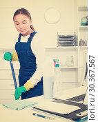 Купить «Young female cleaner polishing surfaces at office», фото № 30367567, снято 21 апреля 2019 г. (c) Яков Филимонов / Фотобанк Лори