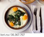 Купить «Top view of fried eggs with spinach, raisins, ham», фото № 30367707, снято 22 апреля 2019 г. (c) Яков Филимонов / Фотобанк Лори