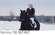 Купить «A woman in a pink hat riding a horse in a village», видеоролик № 30367867, снято 23 июля 2019 г. (c) Константин Шишкин / Фотобанк Лори