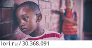 Купить «Schoolkid bullying a sad boy in corridor», фото № 30368091, снято 11 июля 2020 г. (c) Wavebreak Media / Фотобанк Лори