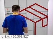 Купить «Сотрудник компании Яндекс открывает ячейку постамата Яндекс», фото № 30368827, снято 20 марта 2019 г. (c) Николай Винокуров / Фотобанк Лори