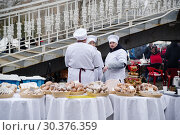 Street trading. Sellers near the trays with baking. Orenburg, Russia - March, 9, 2019: Trade from trays during the celebration of Maslenitsa. Редакционное фото, фотограф Вадим Орлов / Фотобанк Лори