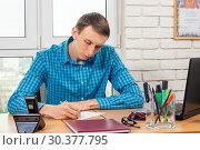 Купить «Молодой офисный специалист за столом пишет заявление», фото № 30377795, снято 17 марта 2019 г. (c) Иванов Алексей / Фотобанк Лори