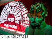 Купить «Девушка прикрывает руками лицо на фоне логотипа Года театра в России 2019 на Московском культурном форуме в выставочном центре Манеж в центре Москвы, Россия», фото № 30377815, снято 22 марта 2019 г. (c) Николай Винокуров / Фотобанк Лори