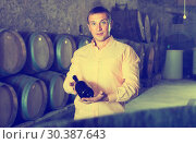 Купить «man with bottle of wine in winery cellar», фото № 30387643, снято 22 сентября 2016 г. (c) Яков Филимонов / Фотобанк Лори