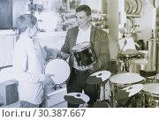 Купить «Father and teenage son examining drum units in guitar shop», фото № 30387667, снято 29 марта 2017 г. (c) Яков Филимонов / Фотобанк Лори
