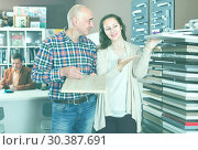 Купить «cheerful family couple looking at kitchen facade in furniture workshop», фото № 30387691, снято 4 апреля 2017 г. (c) Яков Филимонов / Фотобанк Лори
