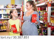 Купить «Woman with daughter are choosing fresh goods in food department», фото № 30387851, снято 5 июня 2017 г. (c) Яков Филимонов / Фотобанк Лори