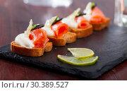 Купить «Delicious sandwiches with salmon, green onions, olives and white sauce on a cutting board», фото № 30389527, снято 26 марта 2019 г. (c) Яков Филимонов / Фотобанк Лори